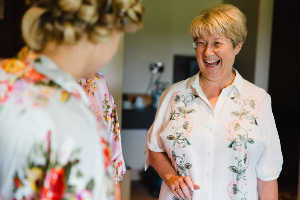 mother of bride sharing joke with bridesmaid