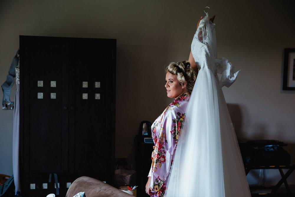 bridesmaid holding up wedding dress