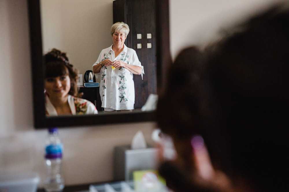 mother of bride looking on at daughter in mirror
