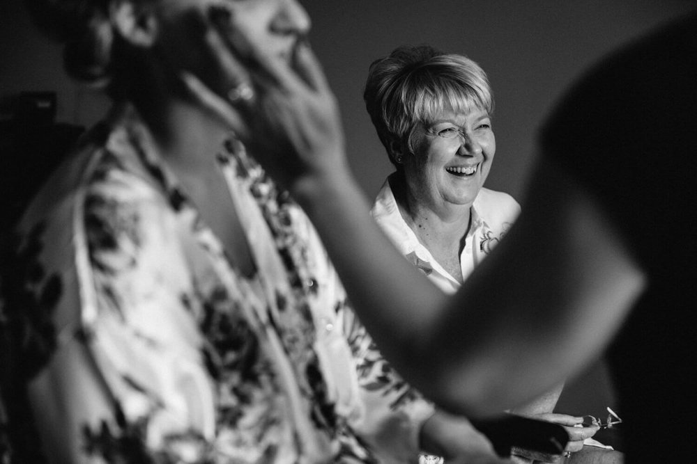black and white photograph of brides mother laughing during make up