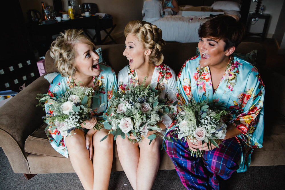 bridesmaids sat together on sofa holding bouquets