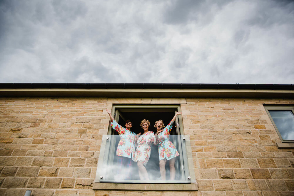 bridesmaids in window posing for camera before ceremony at peak edge hotel