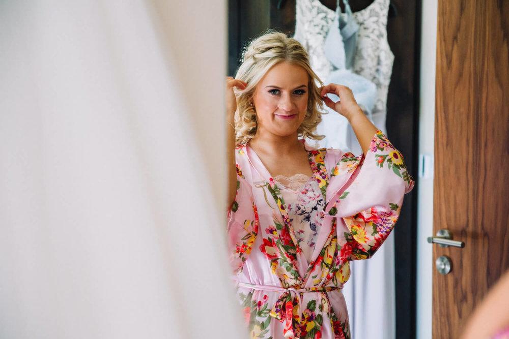 bridesmaid in mirror adjusting hair