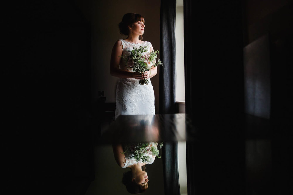 posed reflection portrait of bride holding bouquet in mirror