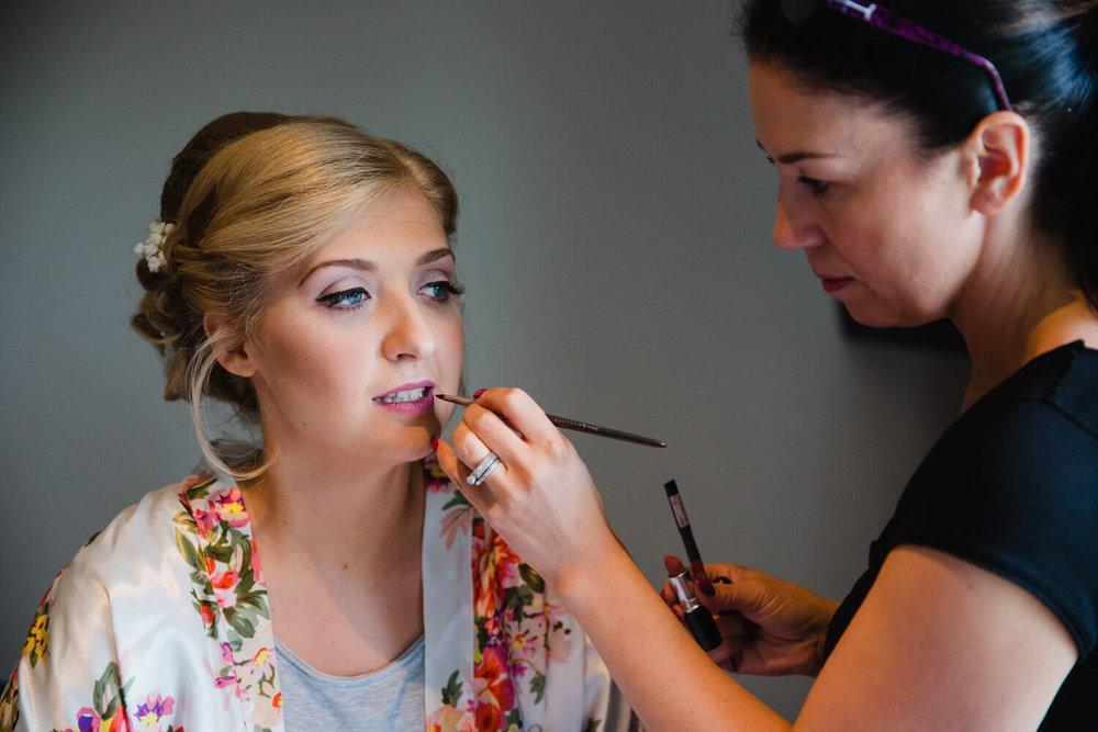bride having lipstick applied before ceremony