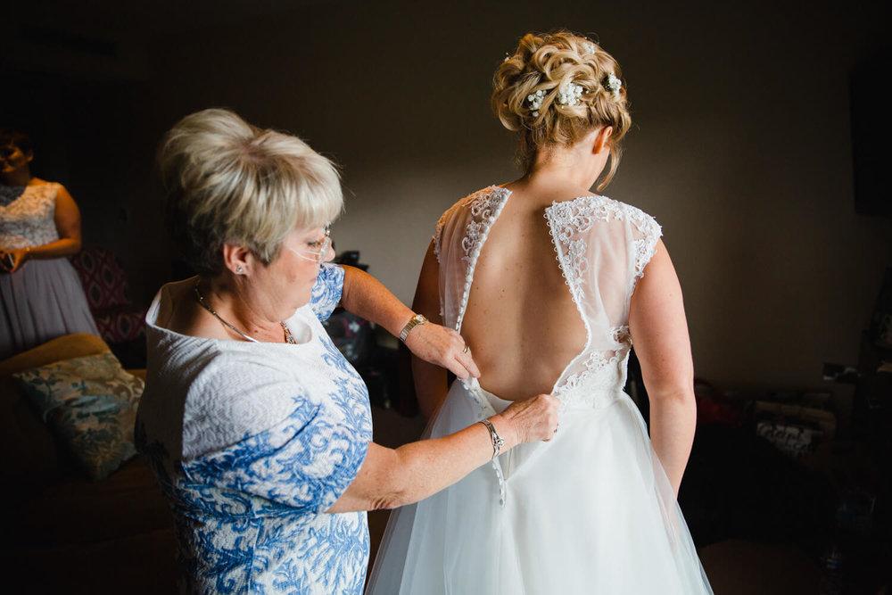 mother of bride fastening back of wedding dress