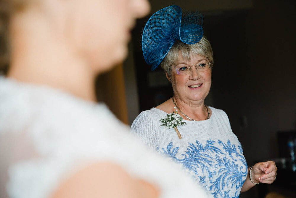 mother of bride dressed in blue with fascinator and pinhole flower