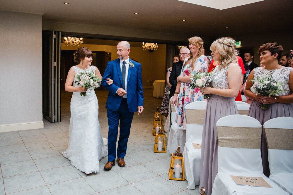 bride walking down aisle with father linking arms