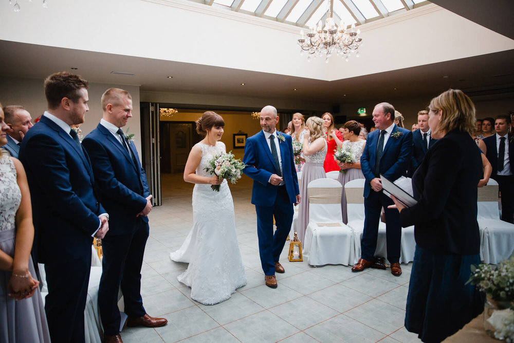 wide angle lens photograph of bride walking down aisle looked on by groomsmen and family