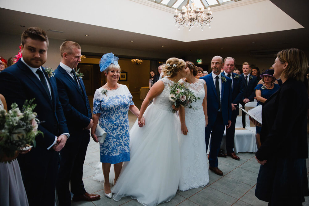 brides share kiss at top of aisle looked on by friends and family