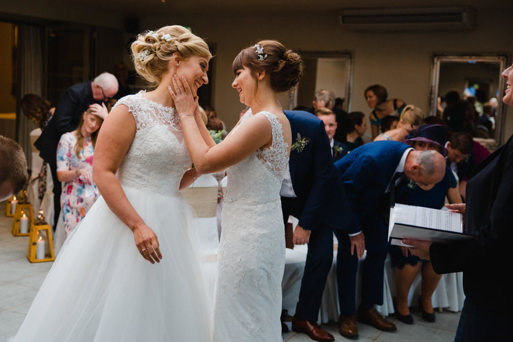 brides share fun intimate moment at top of aisle