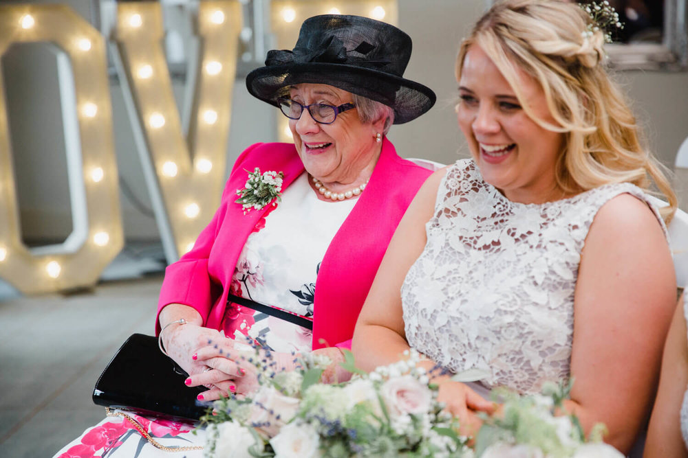 grandma and bridesmaids laughing during ceremony