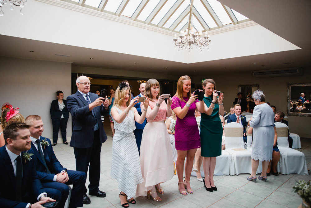 wedding guests hold cameras to take photographs of register signing