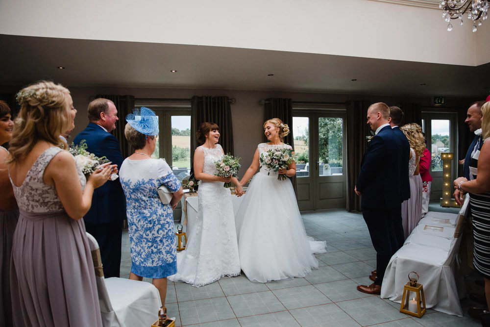 brides holding hands and cheering for ceremony processional