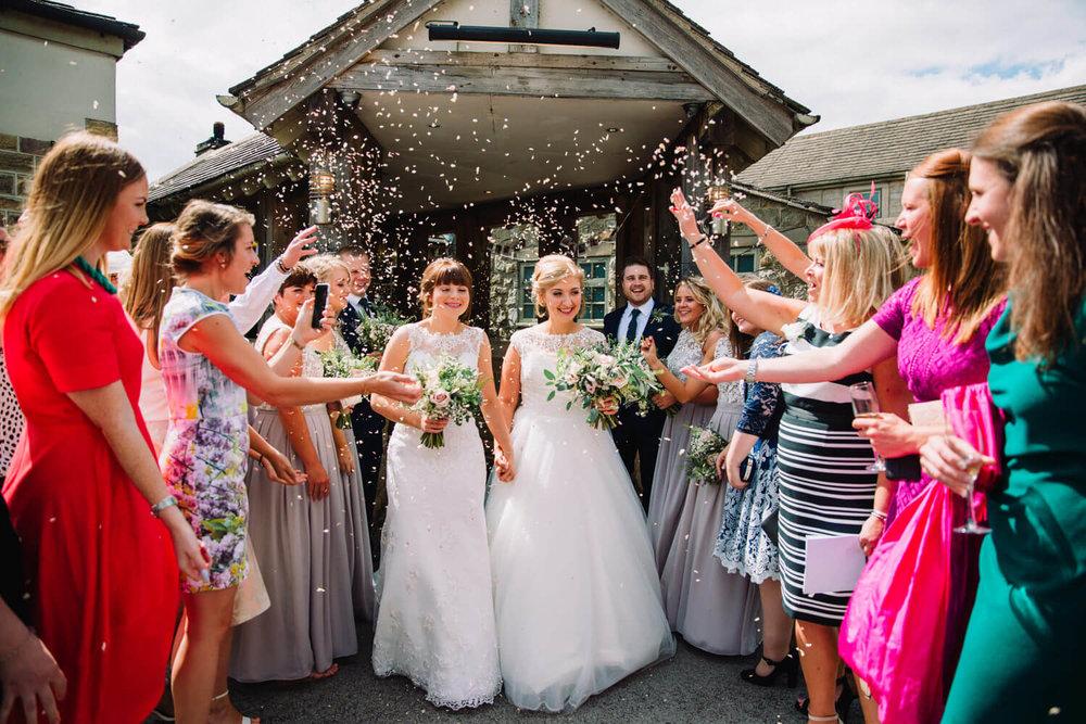 newlyweds walk hand in hand through confetti