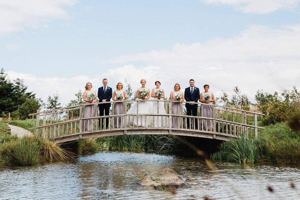 brides and bridal party portrait on bridge