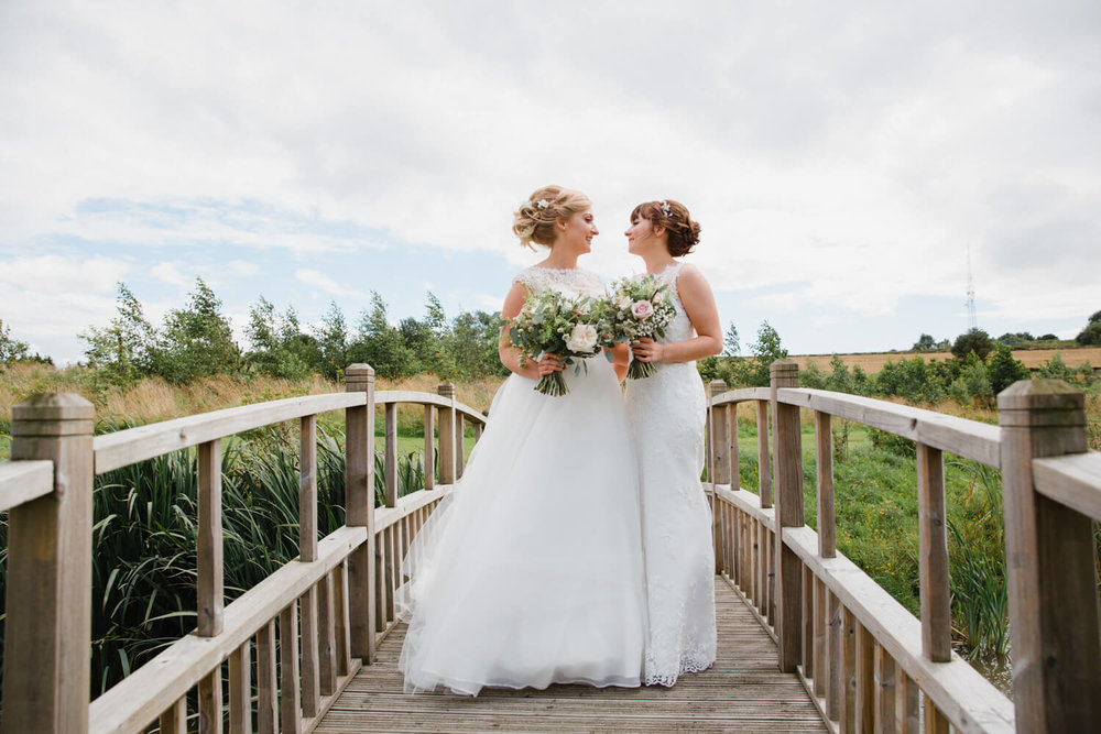 brides hold each other while stood on bridge at peak edge hotel