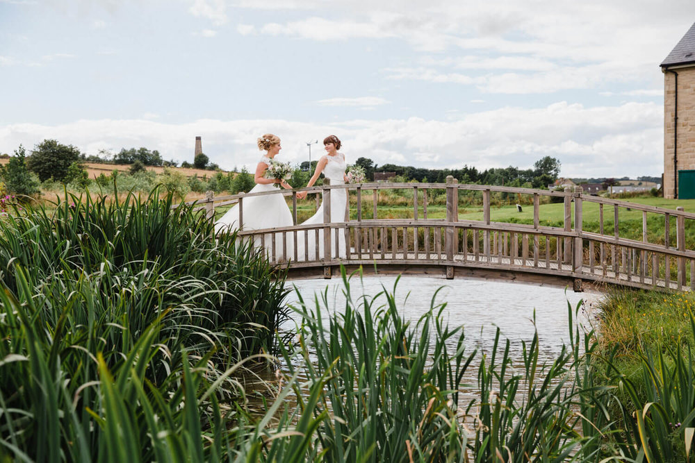 wide angle lens landscape photograph of newlyweds holding hands while crossing bridge