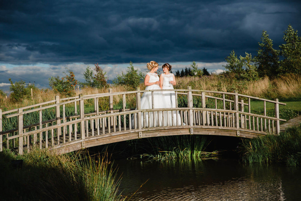 brides hold champagne flutes while stood on top of bridge