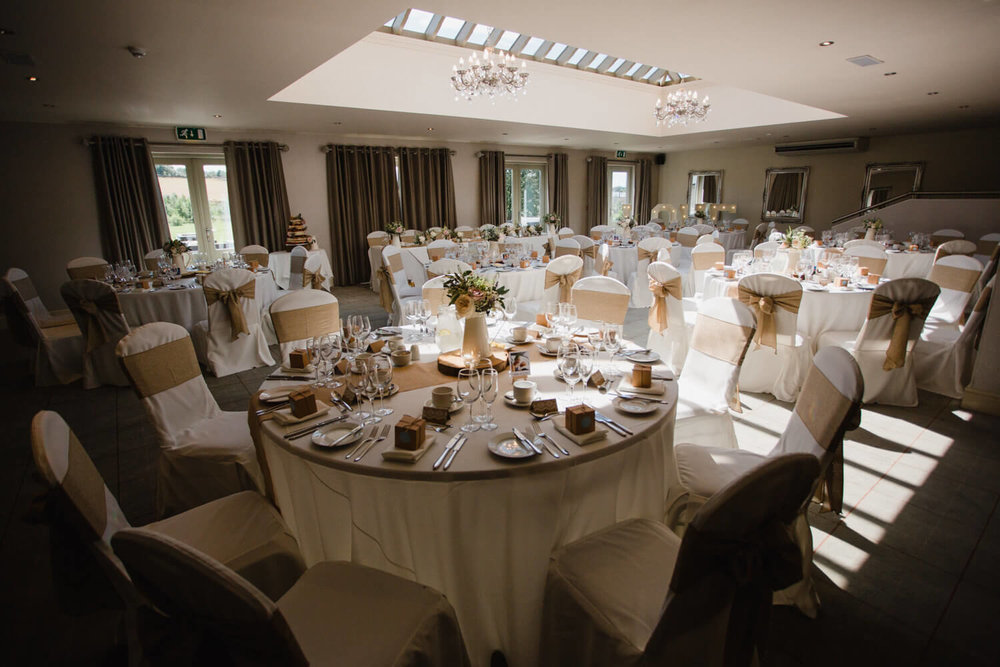 wide angle lens photograph of wedding breakfast room set up with top table and guest tables