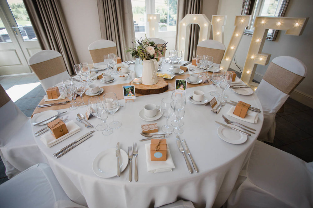 wide angle lens photograph of guest table and love lettering