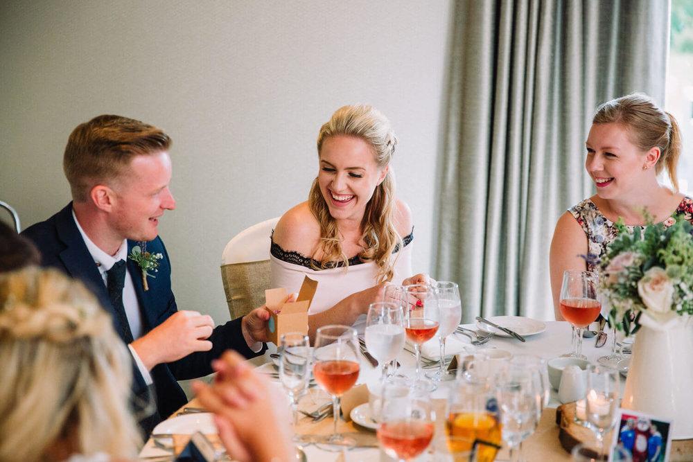 guests sharing joke on wedding breakfast table