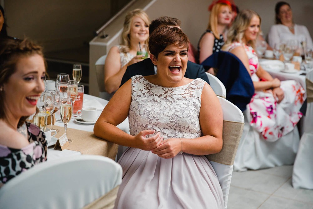 bridesmaid laughing out loud at wedding speeches