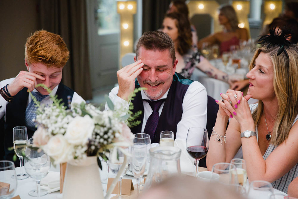 wedding guest with head in hands during best man speech