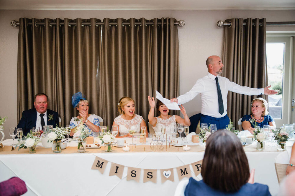 wide angle photograph of groom on top table making bride laugh out loud