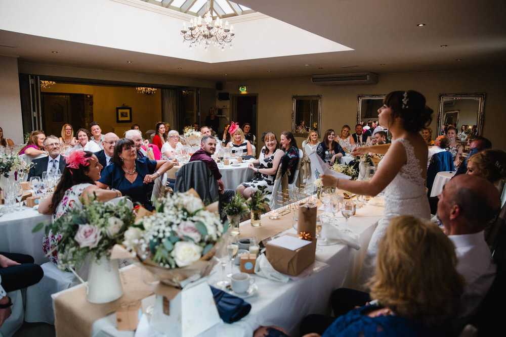 wide angle photograph of wedding party listening to bride speech at peak edge hotel