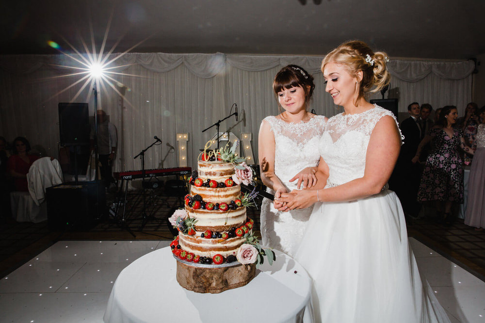 brides cut wedding cake together on dance floor