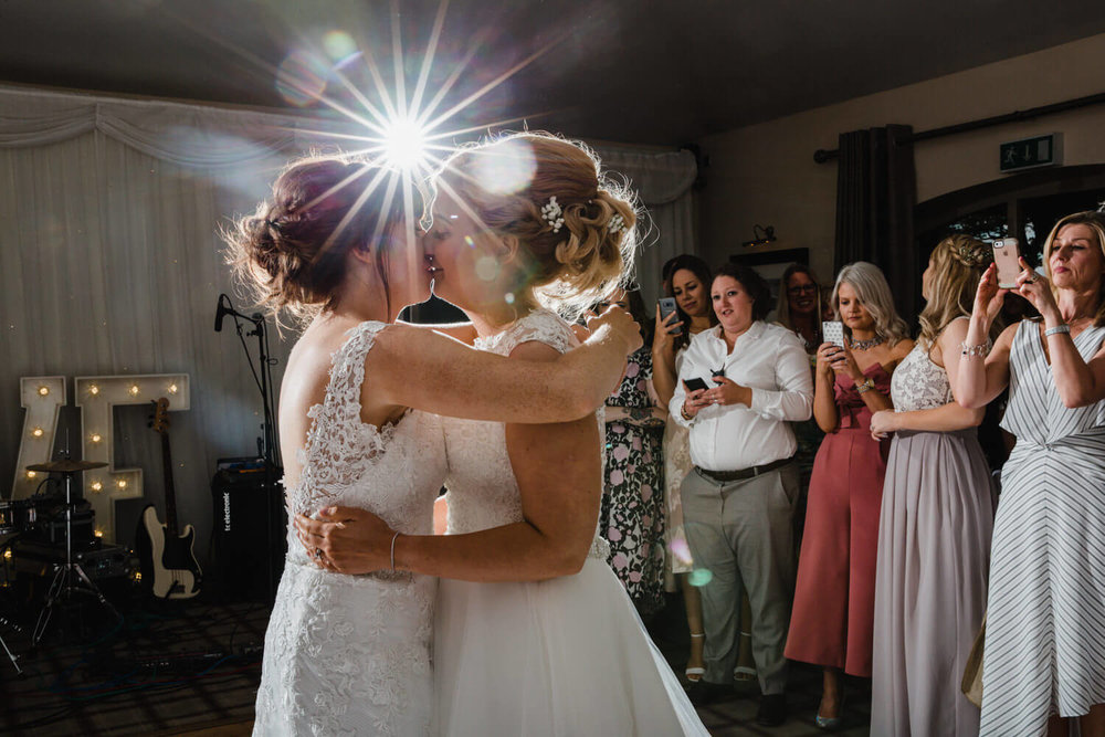 first dance kiss lit up with camera flash causing flare in lens