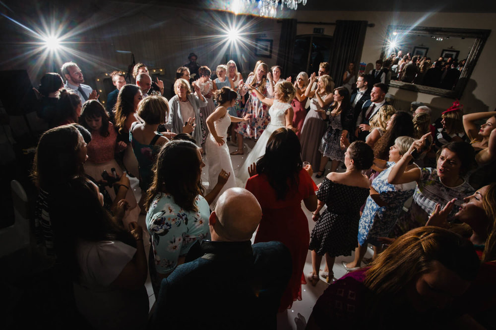 wide angle lens photograph of wedding party dancing together lit up with lens flare camera flashes