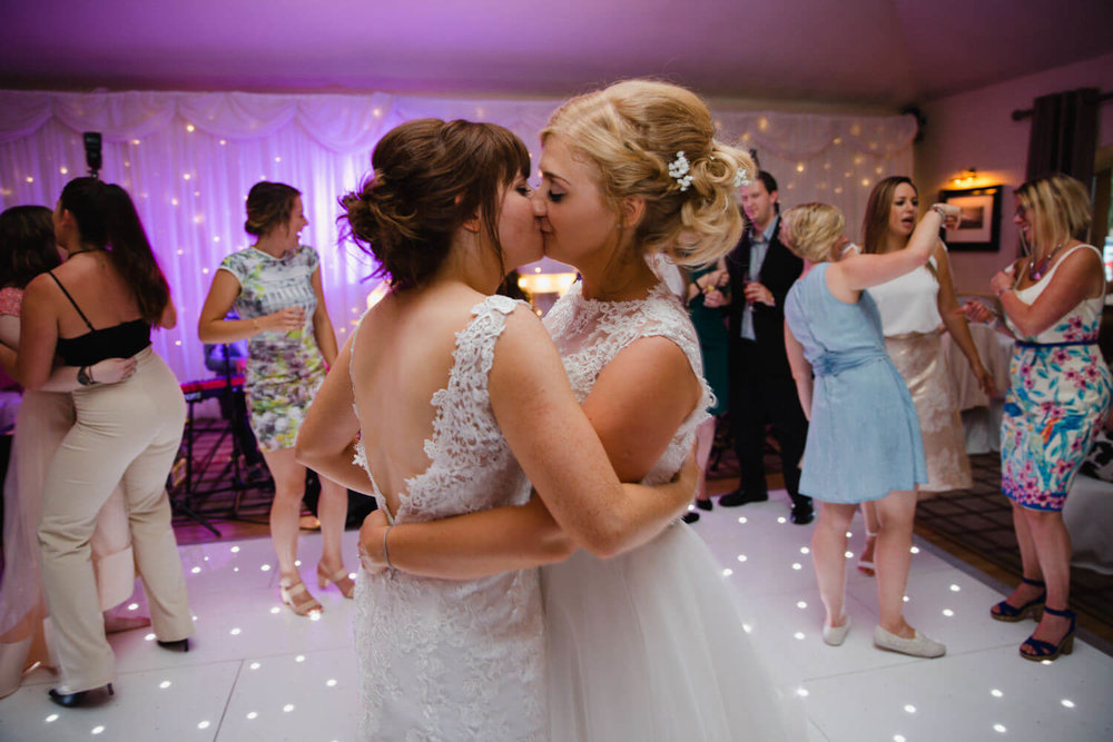 brides kissing on dance floor