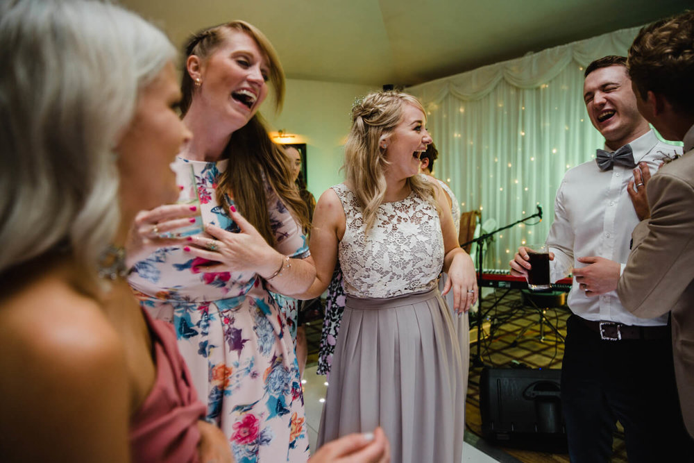 bridesmaid dancing and laughing with groomsman