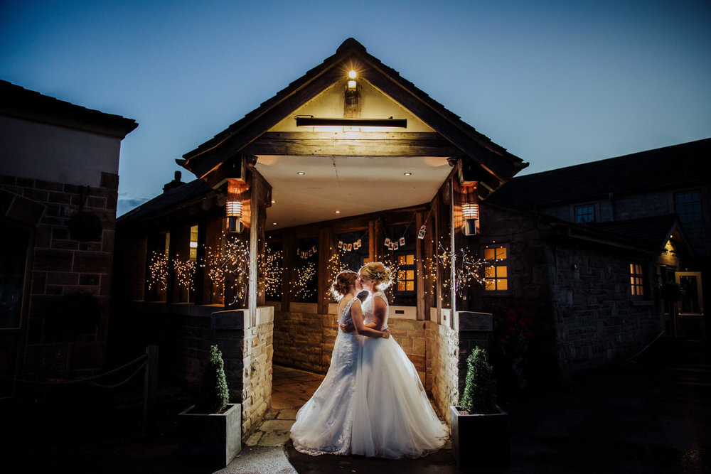 night lit low exposure photograph of brides kissing in entrance lobby of hotel