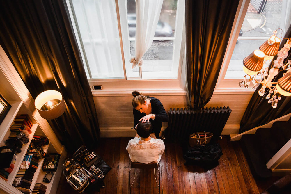 wide angle lens photograph of bride having make up overlooking street