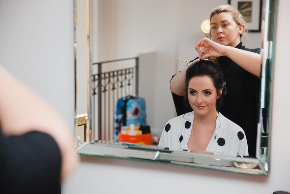 bridesmaid having hair styled in mirror