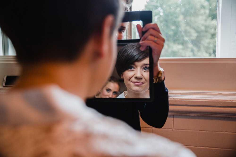 bride looking in mirror after hair styled