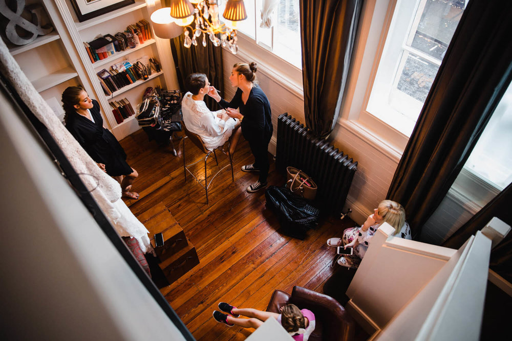 wide angle photograph of bridal party chatting with bride