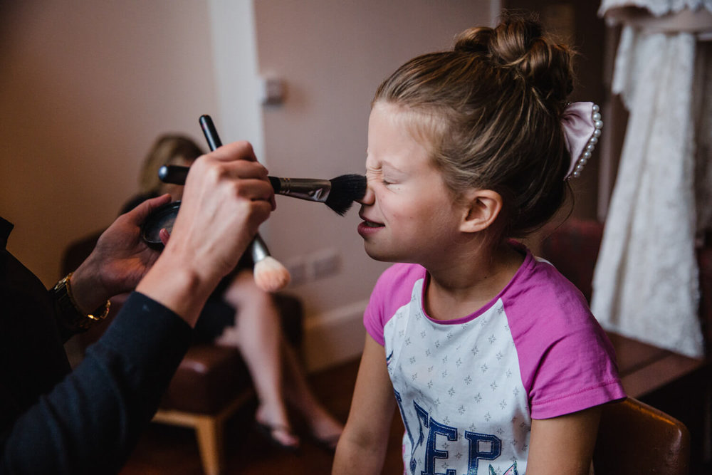 flower girl having make up applied by brush