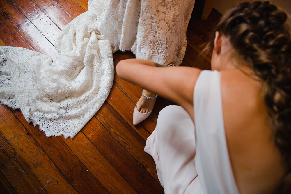 bridesmaid fastening up wedding shoes before ceremony