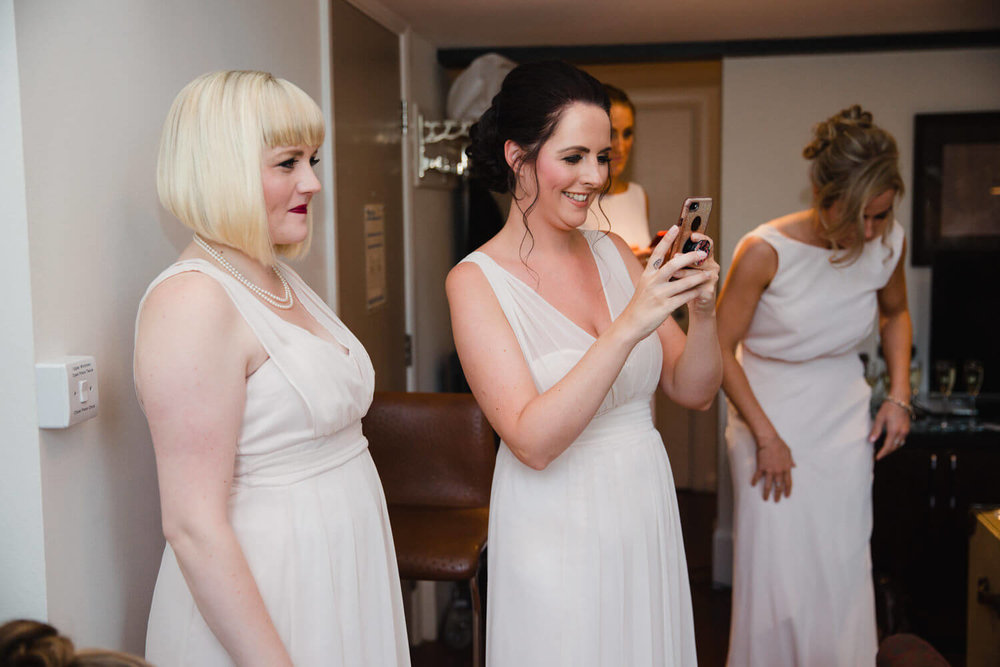 bridesmaids holding camera phones photographing bride