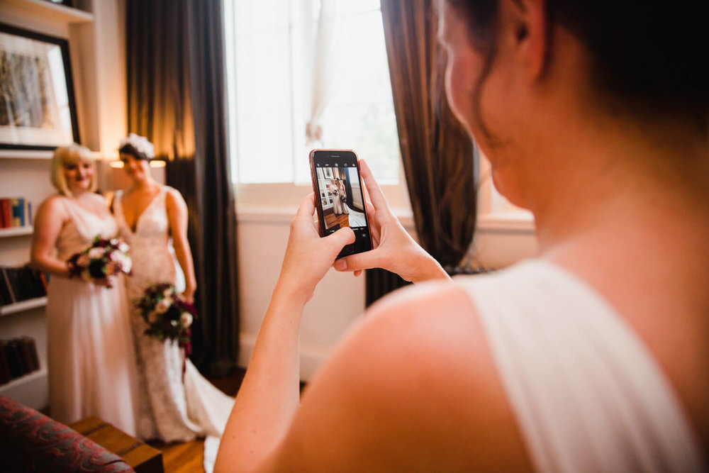 bridesmaid photographing bride with focus on camera phone