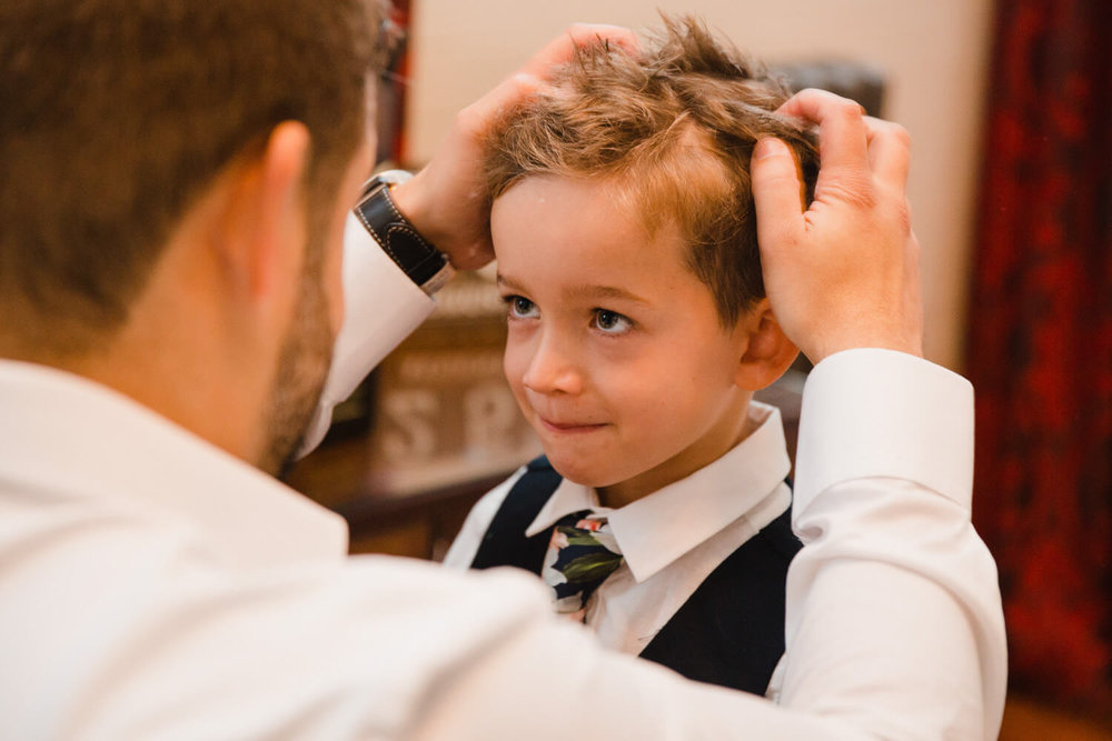 close up macro lens photograph of page boy having hair styled by groom