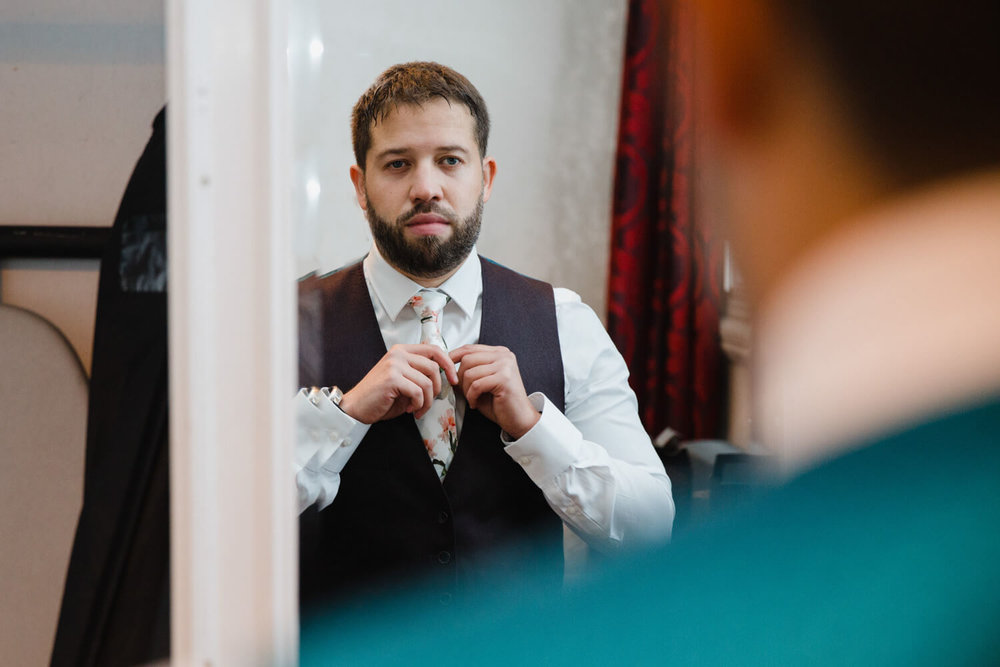 groom adjusting tie in mirror at great john street