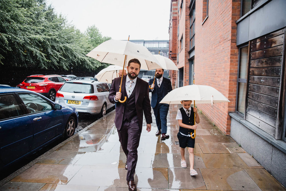 groom and page boy walk down street in the rain