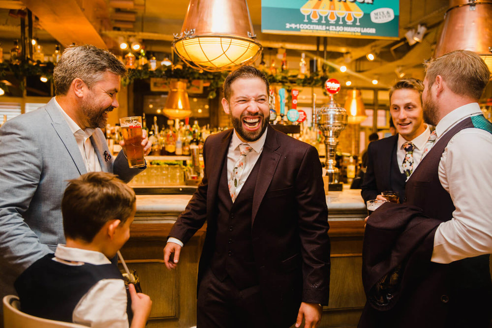 groomsmen at bar laughing and joking
