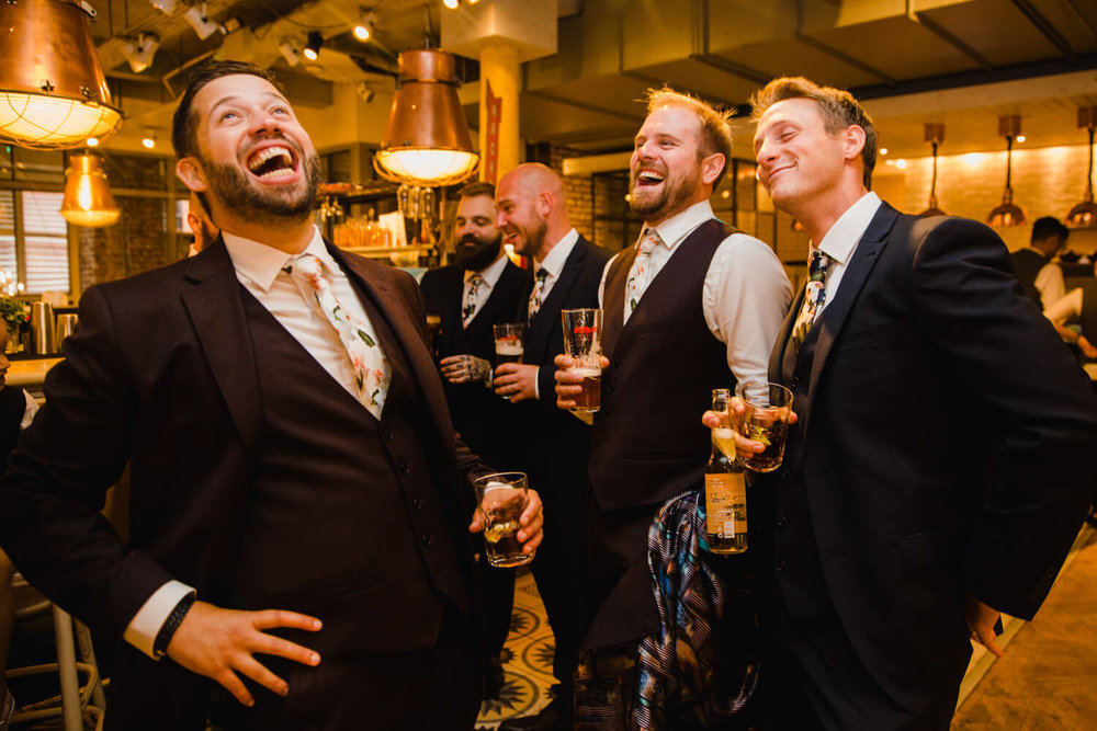 groom shares jokes with ushers with drinks