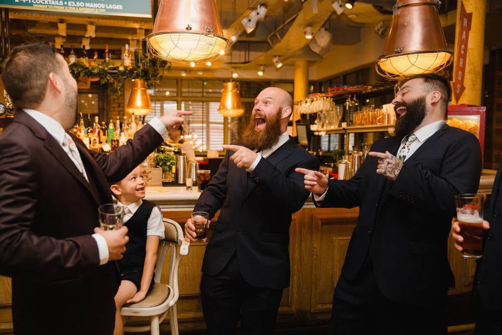 groomsmen laughing and pointing at groom at the bar